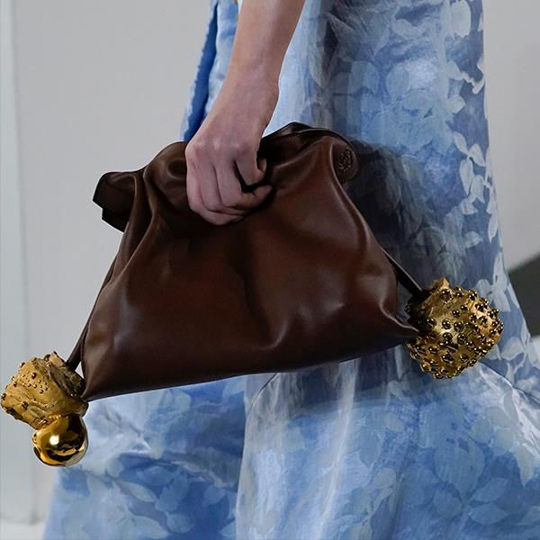 """**Naomi Smith, Fashion Director** <br><br/> """"I usually wear a lot of black, so Jonathan Anderson's modern take on the clutch at Loewe will give a fresh update to my outfits. The khaki, almost chocolate-like leather pairs beautifully with black and neutrals, and the detailed baubles make the bag feel like it's a jewellery statement and clutch all in one."""""""