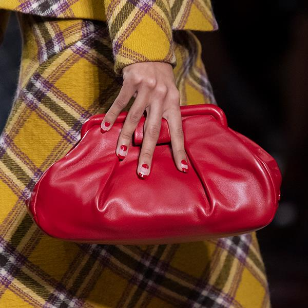 """**Samantha Wong, Market Editor** <br><br/> """"I'm all about a coordinating set right now, and this Miu Miu pairing of a ladylike check suit with a clutch gives an elegant nod to the bygone era. The cherry red complements the mustard perfectly, also adding a punch of colour to my usual neutral-toned outfits."""""""