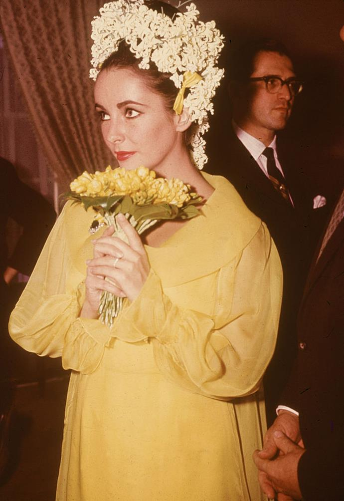 **Elizabeth Taylor (1964)** <br><br> Iconic actress Elizabeth Taylor wore statement yellow (accompanied by a suitably major floral hairstyle) to marry her fifth (and sixth...) husband and *Cleopatra* co-star, Richard Burton, in 1964. This wasn't the first time Taylor had worn colour to wed, either—for her previous marriage to singer Eddie Fisher, she wore an unexpected, elegant shade of green.