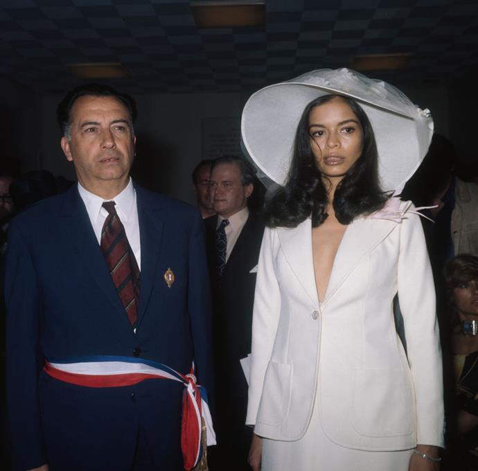 **Bianca Jagger in Saint Laurent (1971)** <br><br> Who knew that a last-minute bridal outfit would result in such an iconic look? For her 1971 marriage to Mick Jagger, Bianca Jagger paired a Yves Saint Laurent blazer with a white slip skirt, as well as a sunhat adorned with white flowers and a delicate layer of tulle. The rest, as they say, is bridal fashion history.