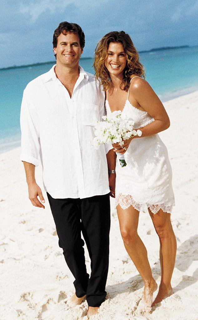 """**Cindy Crawford (1998)** <br><br> Few stars' wedding gowns are more memorable than Cindy Crawford's John Galliano mini-dress, which she wore to marry Rande Gerber in the Bahamas in 1998. <br><br> Of choosing a dress for the secret wedding, Crawford told *People* in 2016: """"I actually told a stylist friend of mine that I had to go to a black-and-white party, so to bring me some black dresses and some white dresses, because we didn't tell anyone we were getting married. That was just one of the white dresses and it was perfect."""""""