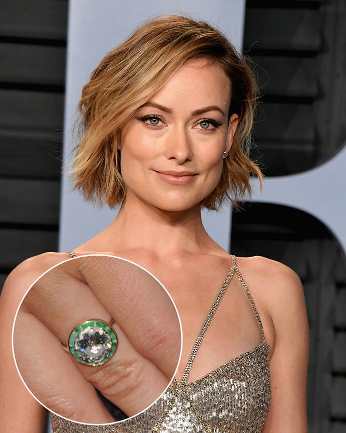 "**The wearer:** Olivia Wilde<br><br> **The ring:** A round-cut diamond surrounded by an emerald halo.<br><br> **The story:** Olivia Wilde's vintage ring from Jason Sudeikis came with a beautiful history, according to the actress and director. ""All they know is that it went through Paris around 1921,"" Wilde told *Brides*. ""I love imagining the story of this ring. Who had it? It's a bit of an aqua emerald, not a deep dark green. Jason said it reminded him of my eyes, which is very sweet."""