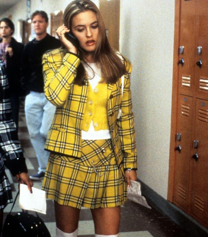 """**Cher's yellow checked suit in *Clueless* (1995)** <br><br> The checked yellow Dolce & Gabbana suit from *Clueless* has been re-done countless times, but you can't deny its impact. Even if it's 'ugly' to some, the two-piece look is perhaps the most quintessentially '90s fashion moment in existence—something the film's costume designer, Mona May, is now fully aware of. <br><br> In a 2015 interview with *[Entertainment Weekly](https://ew.com/article/2015/07/17/clueless-costume-designer-mona-may-chers-yellow-suit/