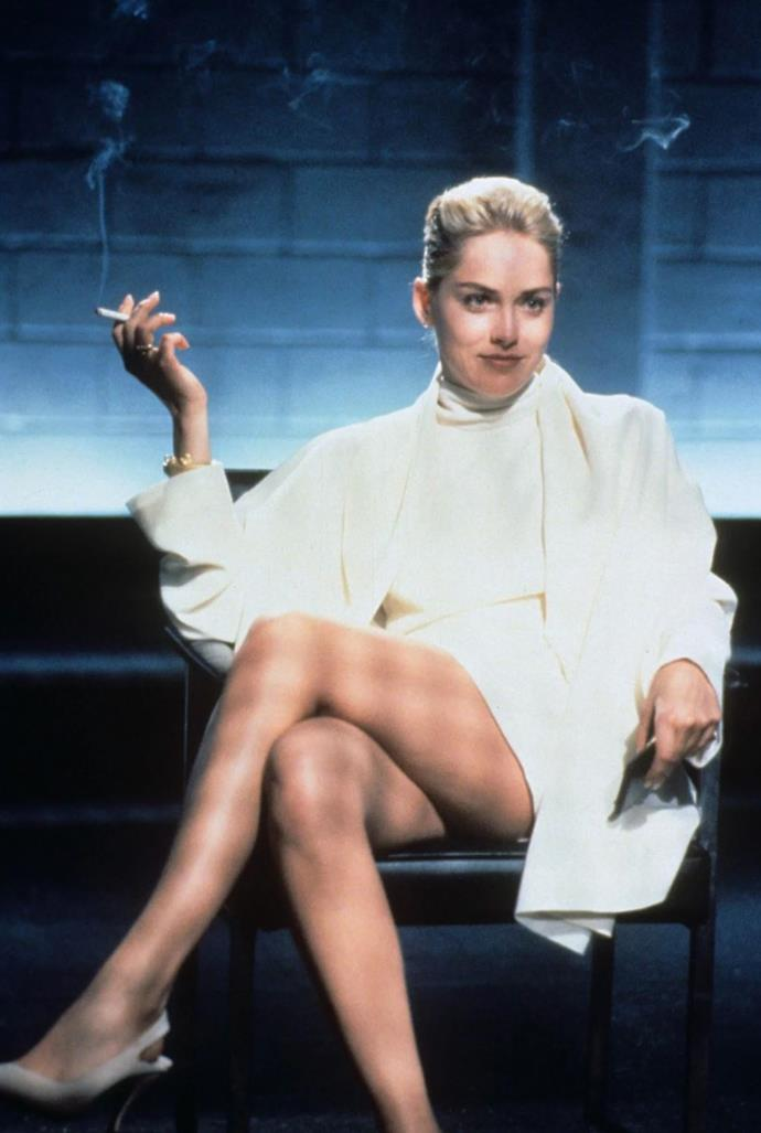 **Catherine Trammel's all-white in *Basic Instinct* (1992)** <br><br> You can't compile a list of controversial on-screen fashion moments without adding *that* white look, comprising of a trench coat and halterneck dress, which was worn by Sharon Stone in *Basic Instinct*. Anyone who's seen the movie knows exactly what happens moments after the above still.