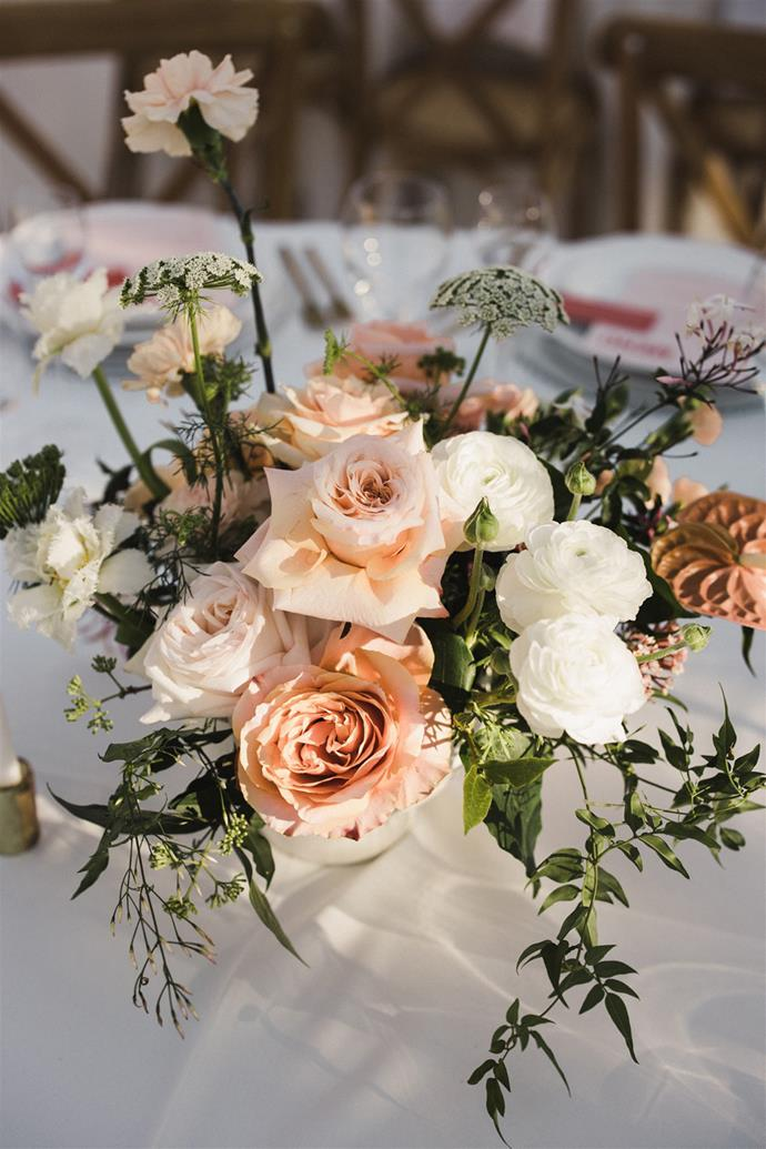 **On the flowers:** The flowers were soft and romantic, with peachy tones, white highlights and green foliage. For the tables we paired tall orchids with large blooming roses in white hand made ceramic vases.