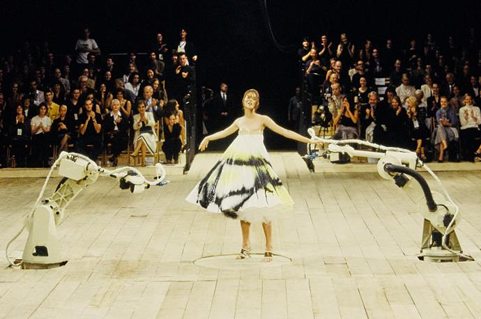 **Alexander McQueen spring/summer '99** <br><br> If McQueen wasn't regarded as the fashion industry's 'enfant terrible' by this point, this was the moment that made him one. With '90s supermodel (and former ballerina) Shalom Harlow closing the show, McQueen had her wear a puffy all-white dress, which was painted by two opposing robots as she spun on a rotating wheel. The result? A truly historic fashion moment.