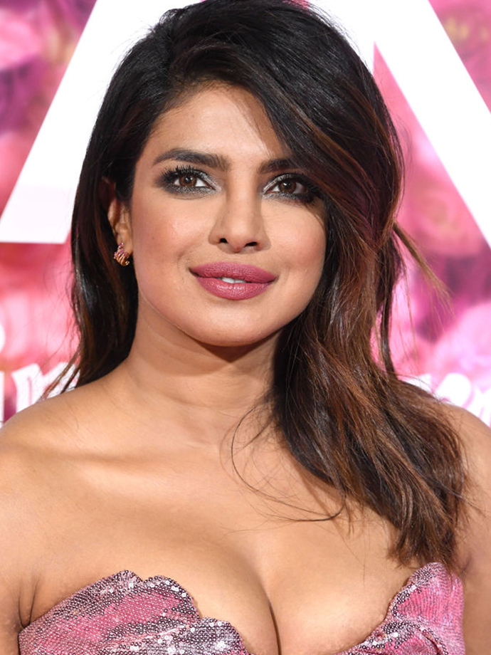 Chopra proves she can do 'soft' as expertly as 'statement', with a boysenberry lip, classic charcoal smoky eye and soft side-swept waves.<br></br> *Via: Getty Images*
