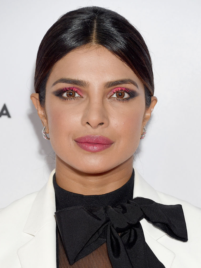 Chopra opts for a cherry-to-charcoal shadow gradient with a sheer tonal strawberry shade tapped lightly onto lips.<br></br> *Via: Getty Images*