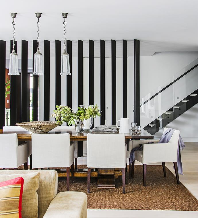 """Vertical steel blades screen the dining room from the hall, creating a sense of drama and rhythmic progression across the space.   For similar **oak table**, try [The Country Trader](http://www.thecountrytrader.com.au/