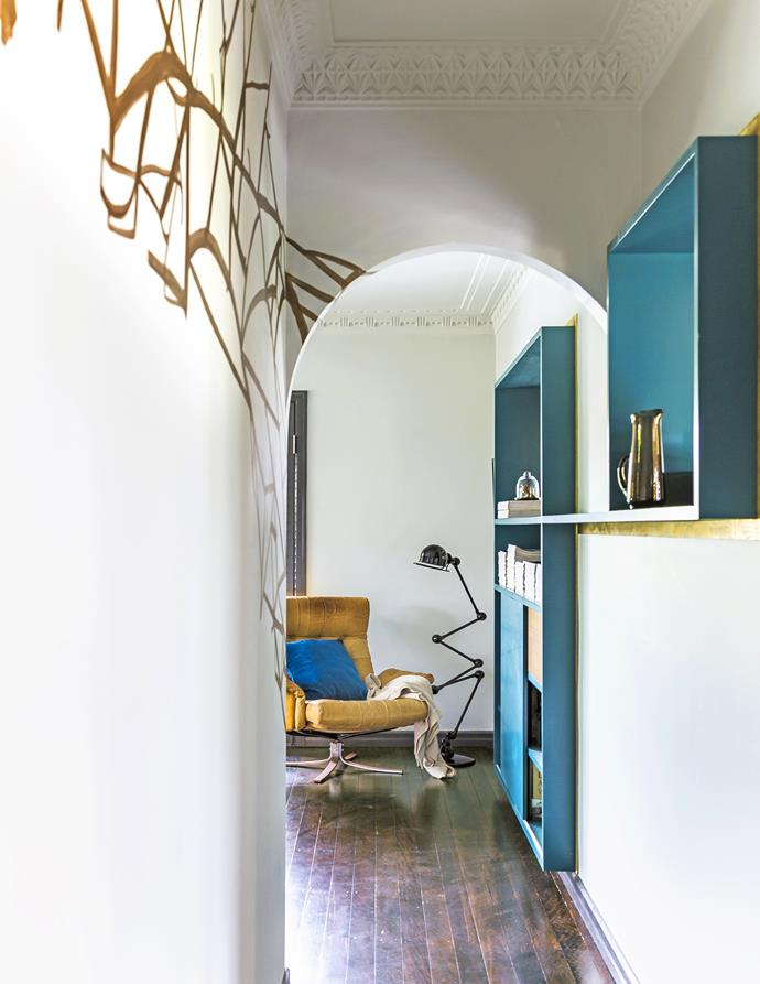 "Rowena used paint to play up the home's architectural details. Here, a branch-like mural points to the Spanish Mission archway. At the end of the hallway is a vintage Ercol armchair, from [Addvintage](http://addvintage.com.au/|target=""_blank""), and loft floor lamp from [Euroluce](http://euroluce.com.au/