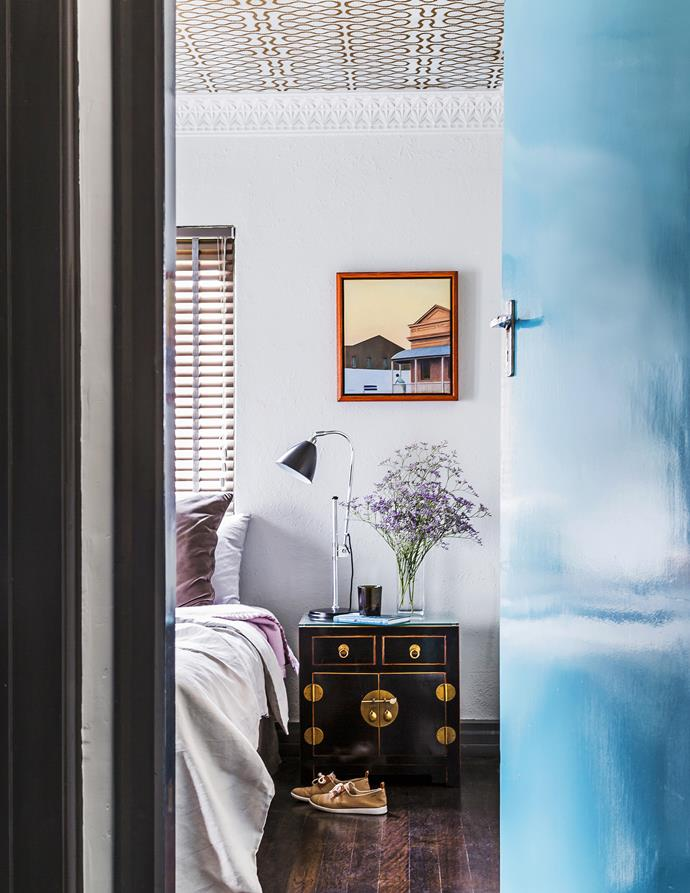 """Both the ceiling and door become features in the main bedroom. The door is painted [Dulux](http://www.dulux.com.au/ target=""""_blank"""") Byron Place to tie in with the cabinetry in the living room while Vivienne Westwood for Cole & Son Squiggle wallpaper from [Radford](http://www.radfordfurnishings.com/ target=""""_blank"""") has been papered on the ceiling. The artwork beside the bed is by [David Band](http://www.davidband.com.au/ target=""""_blank""""). Sitting on the vintage Chinese cabinet is a lamp from [Ikea](http://www.ikea.com.au/ target=""""_blank"""")."""