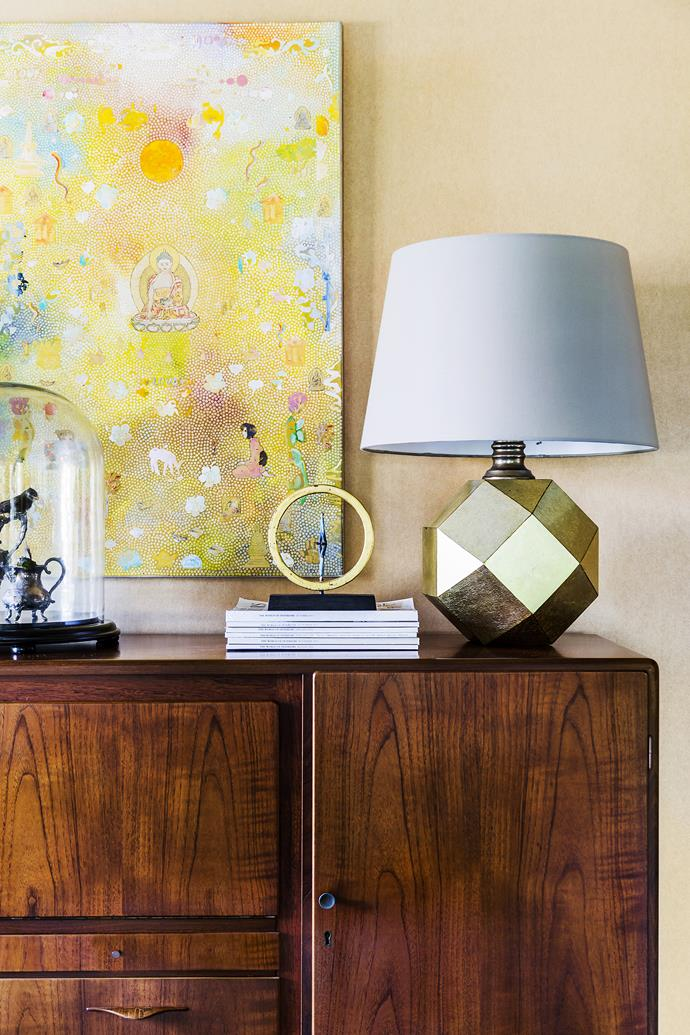 The retro, faceted gold lamp – one of a pair picked up at a garage sale – in the dining area is teamed with a neon artwork by Tim Johnson and a 1950s rosewood sideboard.