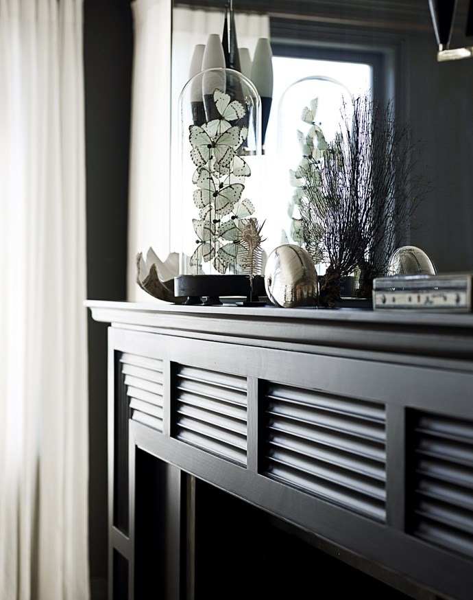 """When revitalising the formal living area, designer Sarah Davison ebonised the timber fireplace with a black stain.   Pair of **wall lights** from [Angelucci 20th Century](http://www.angelucci.net.au/ target=""""_blank""""). Vintage **glass dome** with butterflies bought at a Paris flea market."""