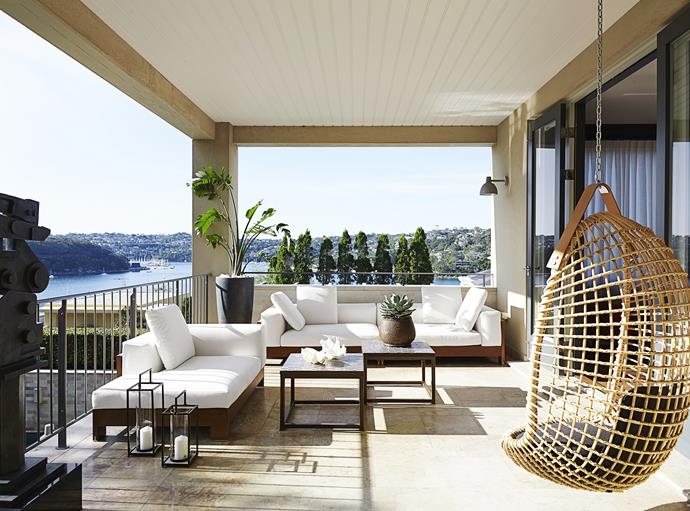 "The terrace off the formal living room offers spectacular Sydney harbour views.   Minotti Alison Iroko **sofa** and **chaise** and Vittorio Bonacina Eureka **hanging cane chair**, all from [Dedece](http://www.dedece.com/|target=""_blank""). **Side tables** sourced in Morocco. **Sculpture** by Robert Klippel."