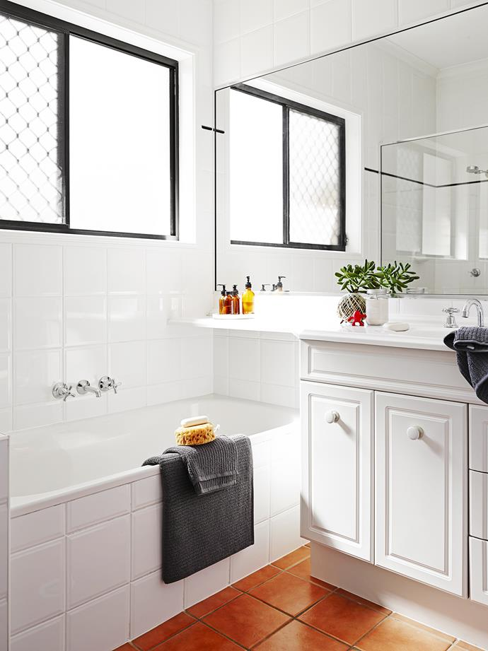 The crisp white bathroom is accentuated by charcoal towels.