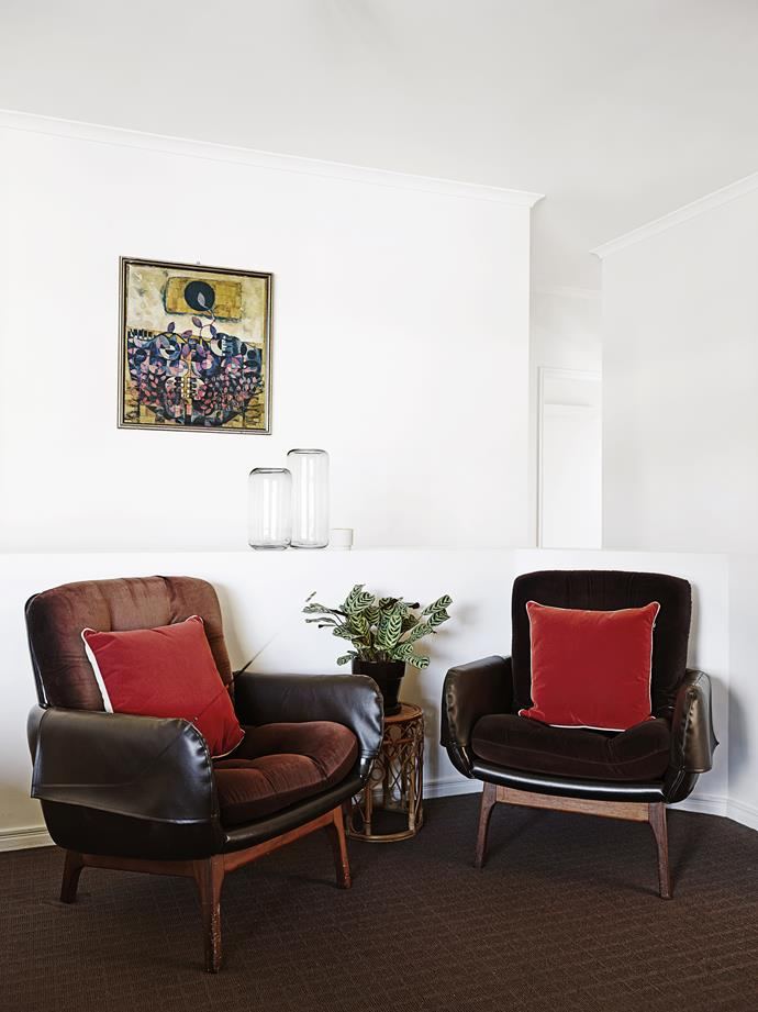 A pair of classic retro armchairs, upholstered in black vinyl, were discovered at a local vintage store.