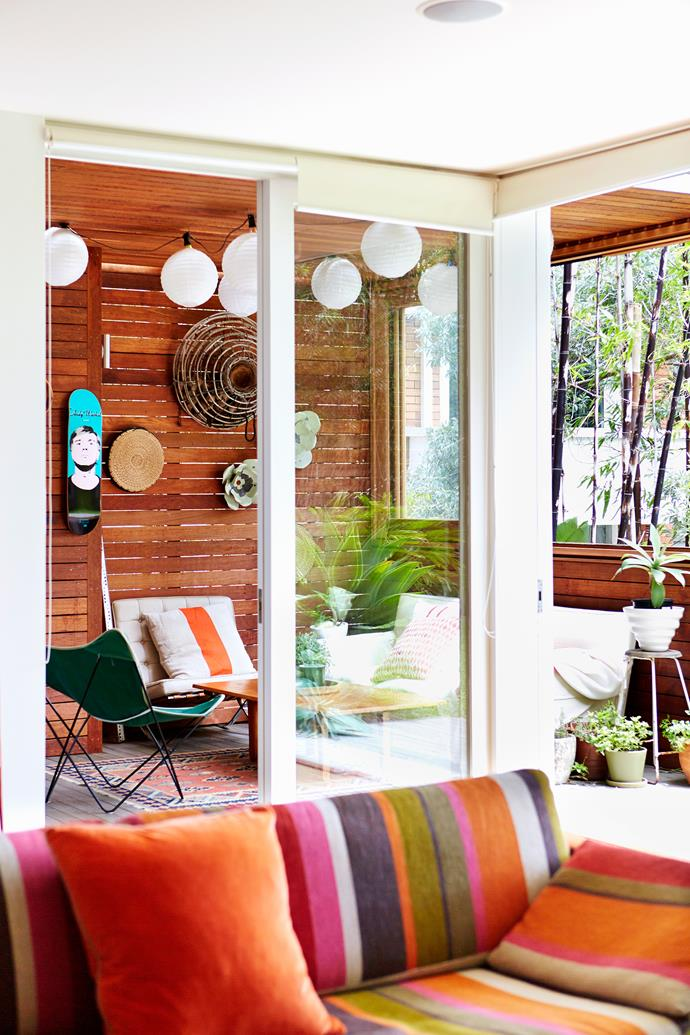 "With a view from the living room, this recent outdoor addition is the owners' favourite spot in the house. ""For parties, we put coloured globes inside the paper lanterns,"" says Alex.   The striped outdoor cushion is from [Maison Montage](http://www.maisonmontage.com.au/