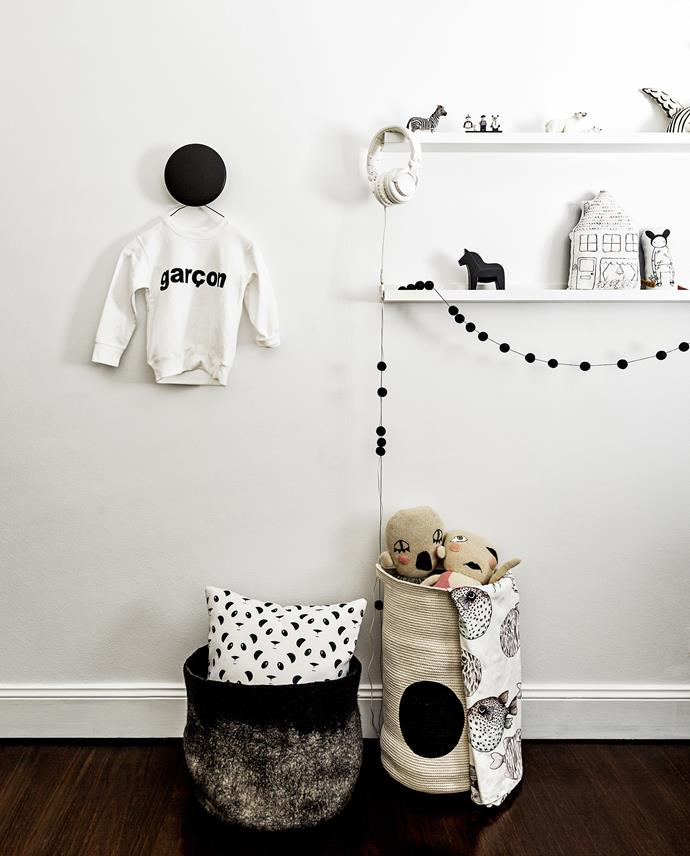 Floating shelves, a large dot wall hook and fabric baskets do double duty to store and display toys, trinkets and clothes.   Photo: Felix Forest / bauersyndication.com.au