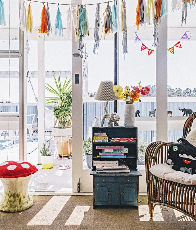 "A tassel garland hangs in front of the window adding playful pops of colour to the simple white room. ""We just went with white walls and a sisal carpet to accommodate our eclectic style and hoarder tendencies – for us, a neutral base allows the objects to be the feature,"" says Xanthe.   Photo: Felix Forest / bauersyndication.com.au"
