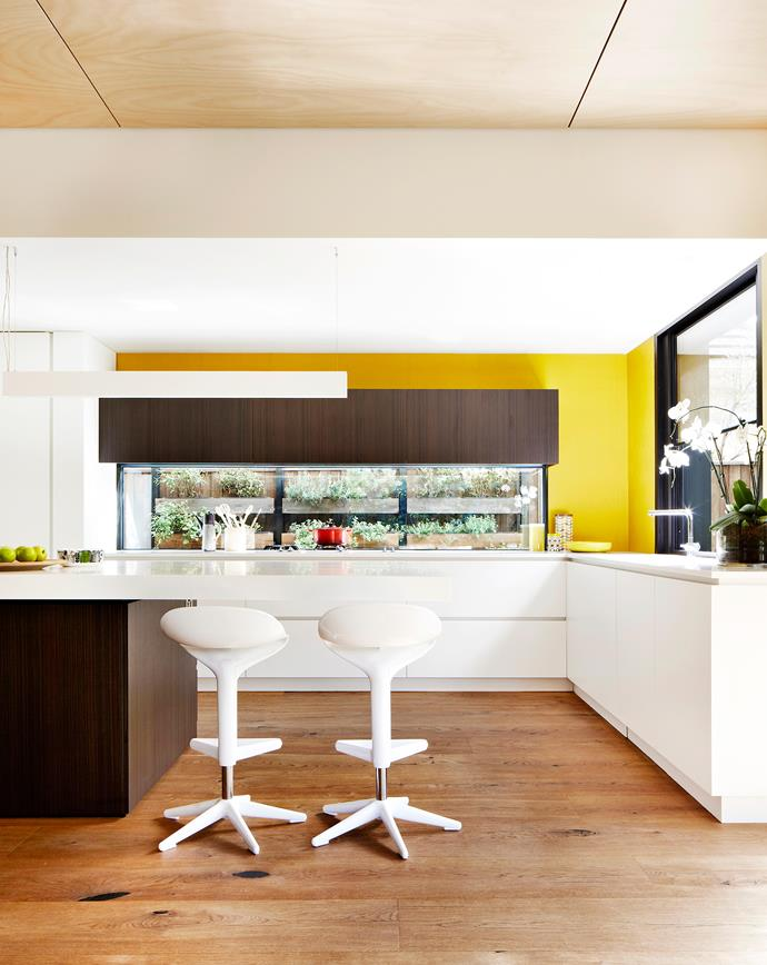 Nicholas and Fiona had planned a marble kitchen, but chancing upon some sunshine yellow vinyl wallpaper changed all that. A mirror-lined cocktail cabinet is concealed within the island bench.
