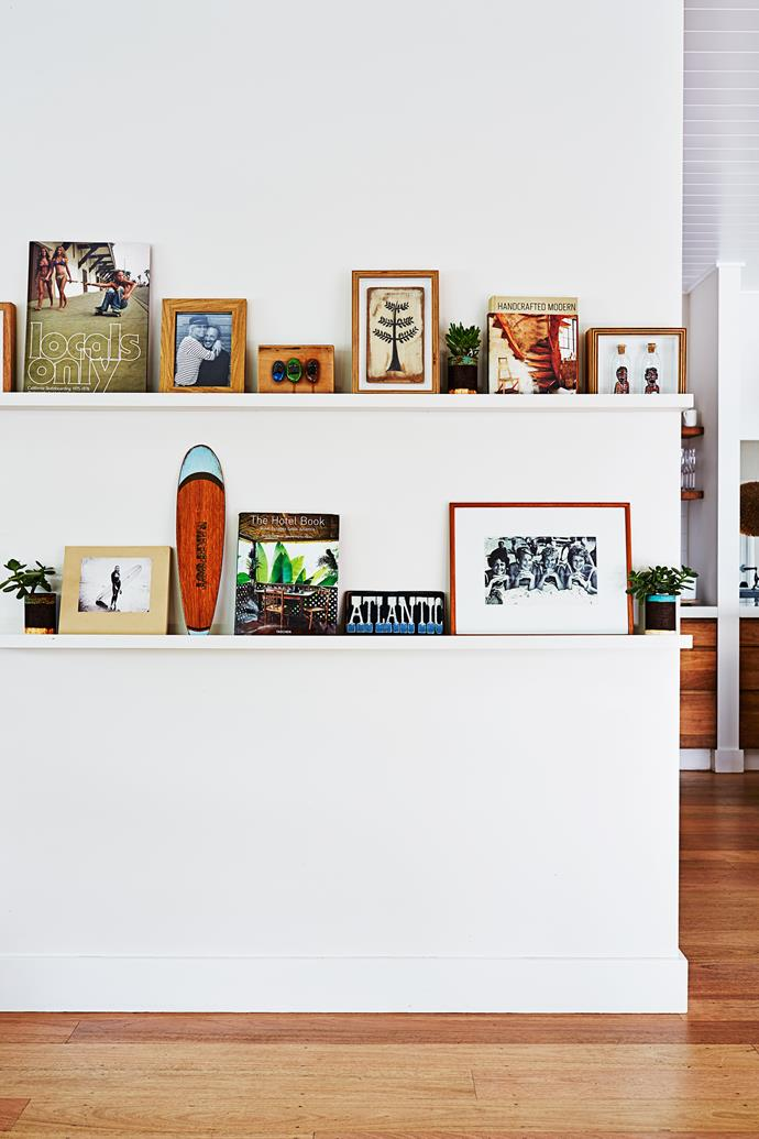 Wall shelves in the living room display family photos, book collections and travel mementos.
