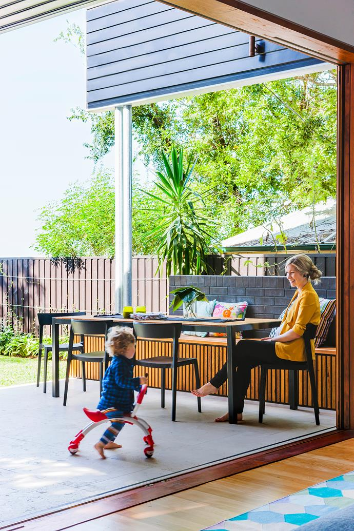 """Kim and two-year-old Harry relax in their home's breezy indoor-outdoor transition space.   Custom **dining table** by [Green Cathedral](http://greencathedral.com.au/