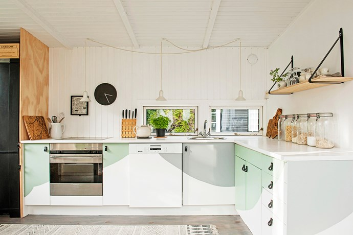 """The existing cupboards of this kitchen were brought to life with a 'wave' pattern of green and grey tones. Old handles were replaced with black-leather straps and dangling pendants installed for a laidback country vibe. Take a tour of [this delightful family cottage](http://www.homestolove.com.au/gallery-cecilia-and-jespers-country-cottage-1682