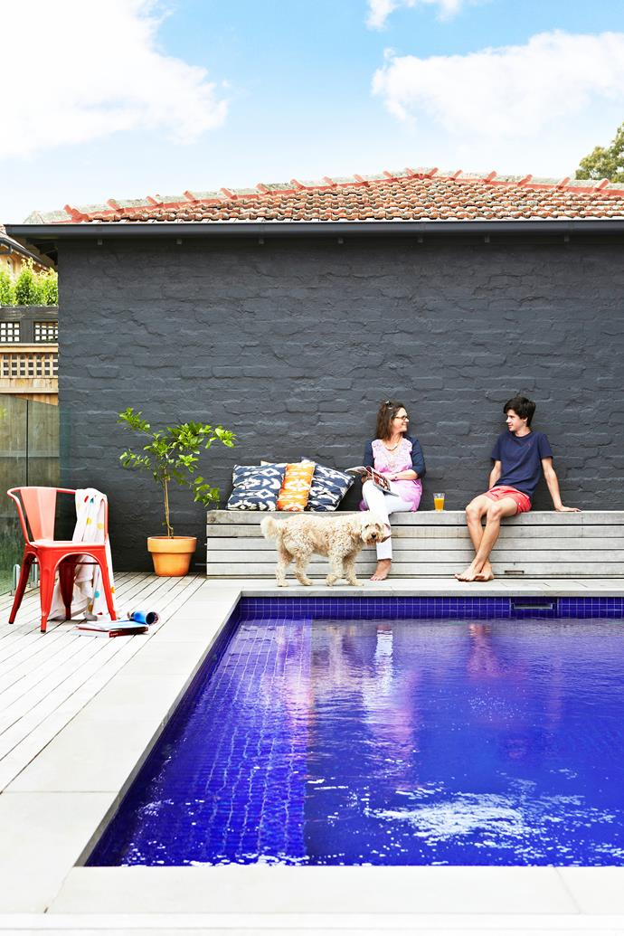 Georgie and her son Ollie catch up on the day's news by the elevated pool which was added during the second renovation of the house.
