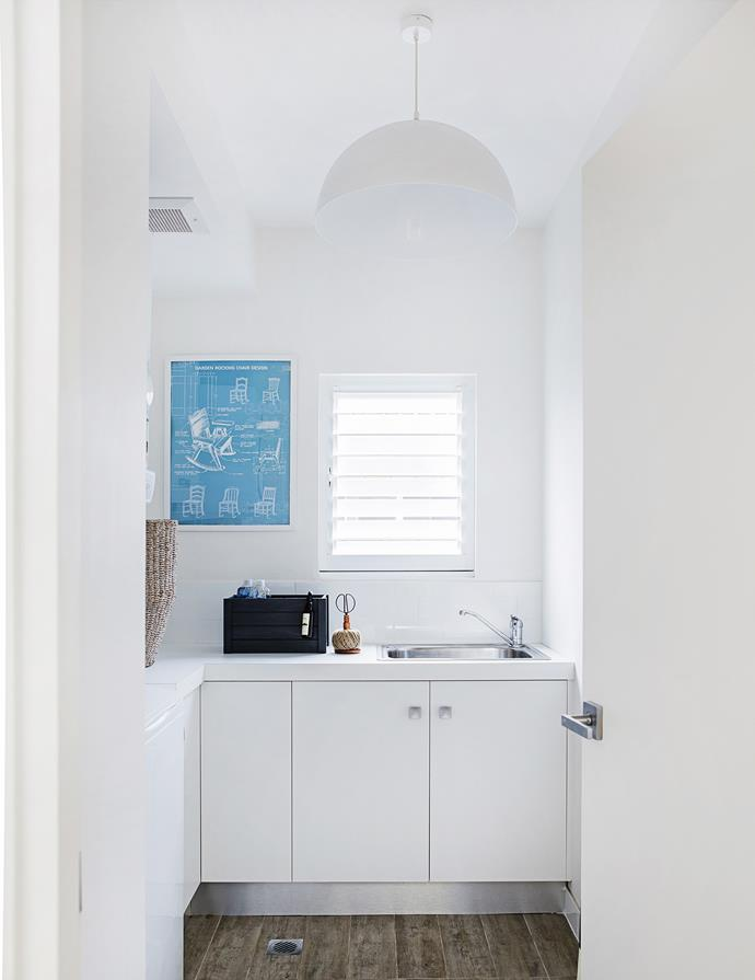 "The large laundry is simply finished with timber-look tiles and plain white laminate. A stylish crate keeps unsightly products out of sight, while an [Ikea](http://www.ikea.com/au/en/|target=""_blank"") print adds interest."