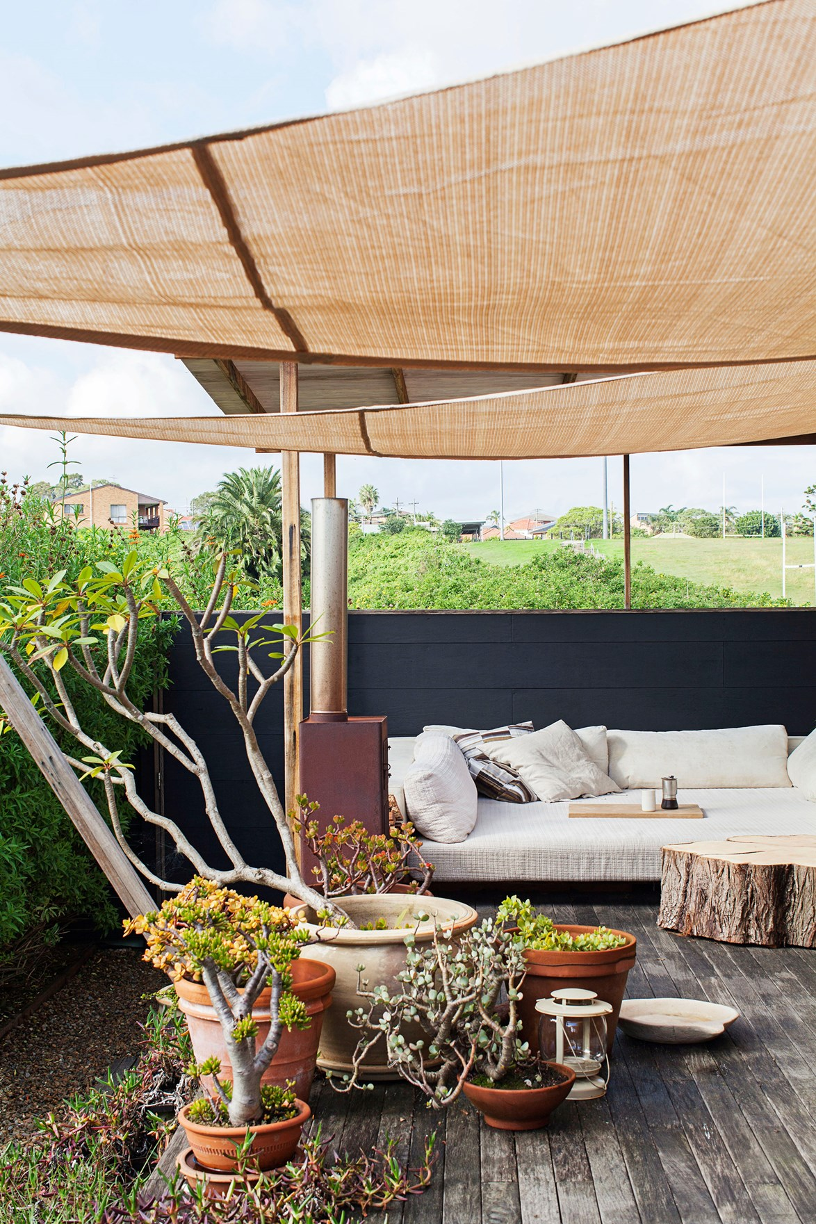 "It's hard to believe this [Scandi-style sanctuary](https://www.homestolove.com.au/gallery-diana-and-noeks-sanctuary-in-the-city-1716|target=""_blank"") is located just minutes from Sydney's CBD. This outdoor day bed, sheltered by a shade sail and surrounded by leafy plants and natural timbers, just adds to the relaxing vibe. Did we mention there is also a meditation tent in the garden nearby?! *Photo:* Francoise Baudet"