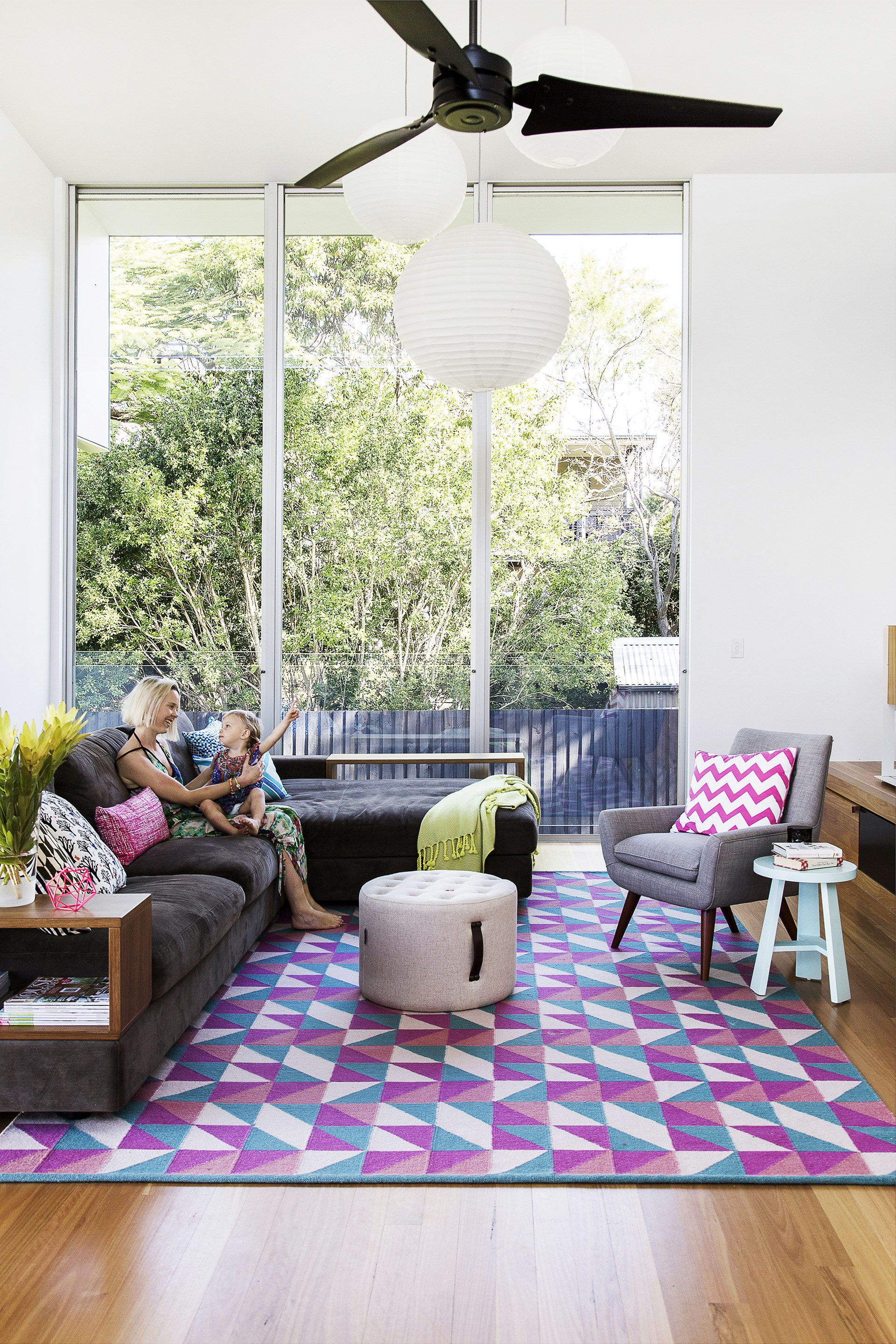 """In this living room, floor-to-ceiling, double-hung windows are shaded by wide eaves. A ceiling fan keeps the air moving on sweltering days. [Read more about this house](http://www.homestolove.com.au/laura-and-alistairs-contemporary-family-home-1720