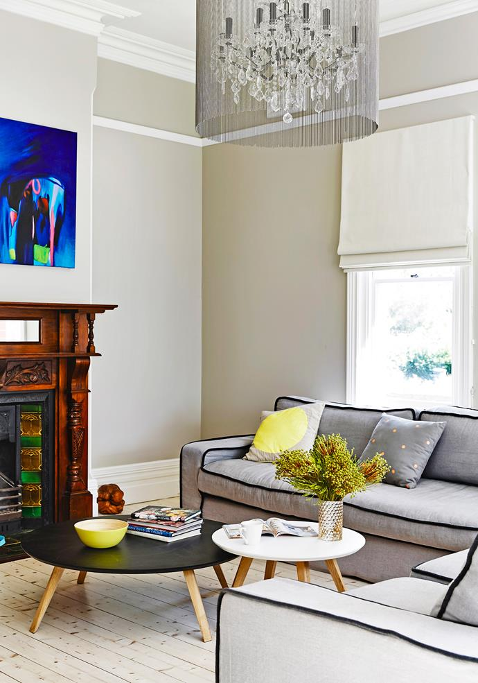 """Period Edwardian features, such as this tiled fireplace, have been retained and restored.   **Coffee tables** from [Luke Furniture](http://www.luke.com.au/ target=""""_blank""""). **Sofa** from Camm Upholstery."""