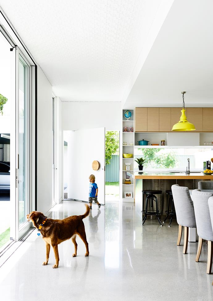 """The design allows for the exterior to be in full view from the kitchen and dining area, so the kids can play safely outdoors.   Circular **door handle** from [Designer Doorware](http://www.designerdoorware.com.au/ target=""""_blank""""). The **pendant light** is an original tramline light, found under the house and repainted."""