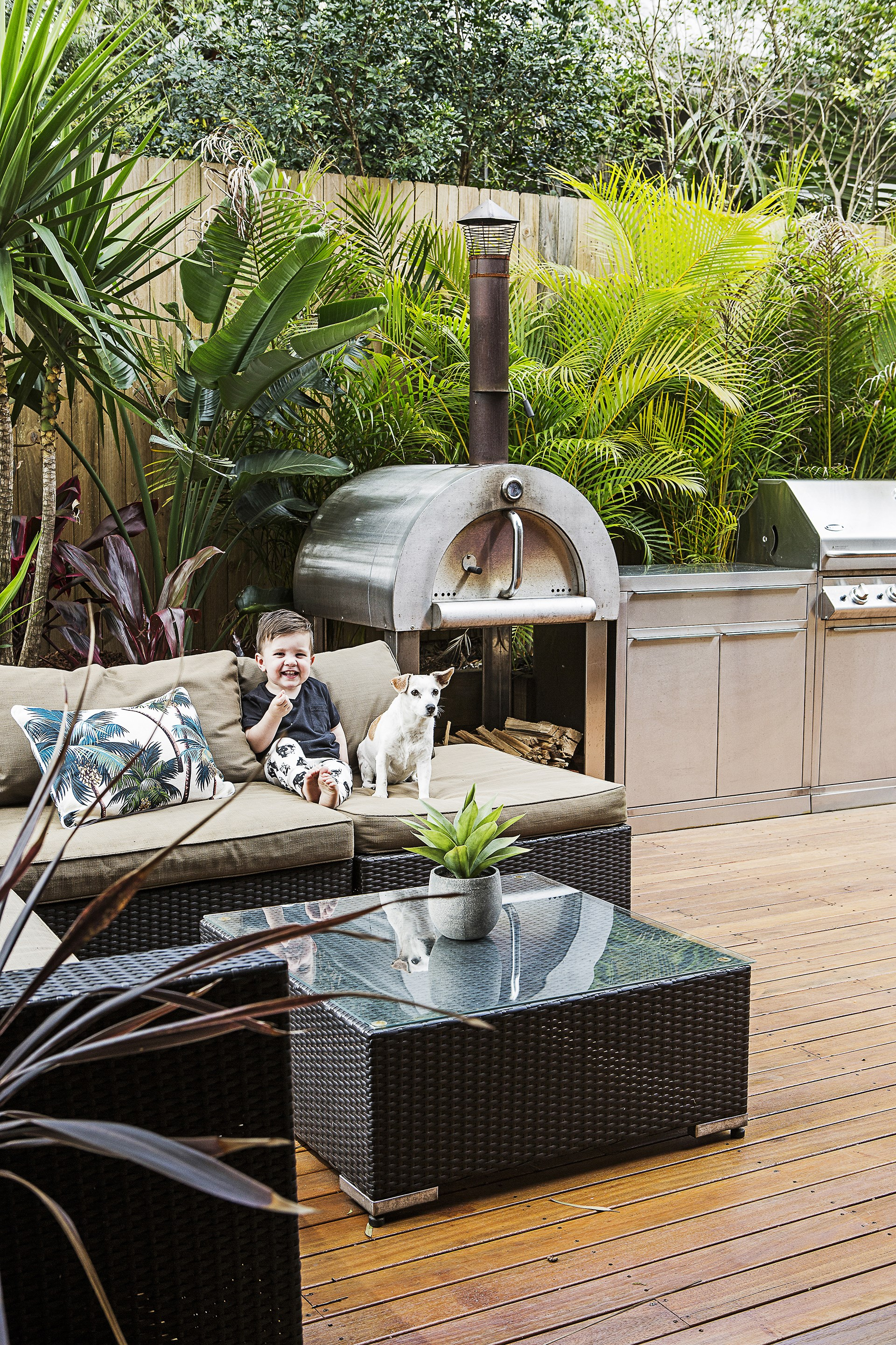 This leafy deck was purpose-built for entertaining and includes a wood-fired pizza oven. *Photo:* Maree Homer.