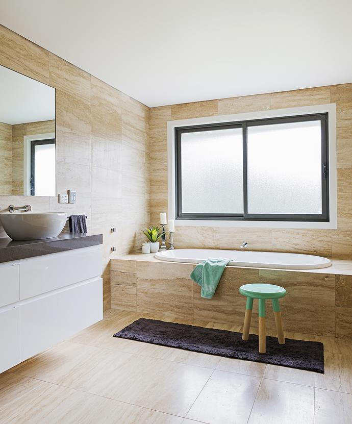 Travertine tiling is the hero in this mellow-toned bathroom, with just a subtle splash of colour.