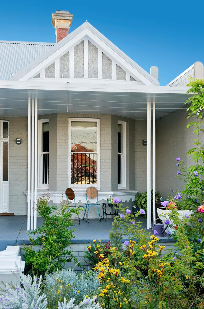 The home's facade expresses its evolution: a Federation-era bay window and gable detail sit easily alongside the clustered supports and flat-roof verandah awning. Plants include pomegranate, native hibiscus and yellow kangaroo paw.