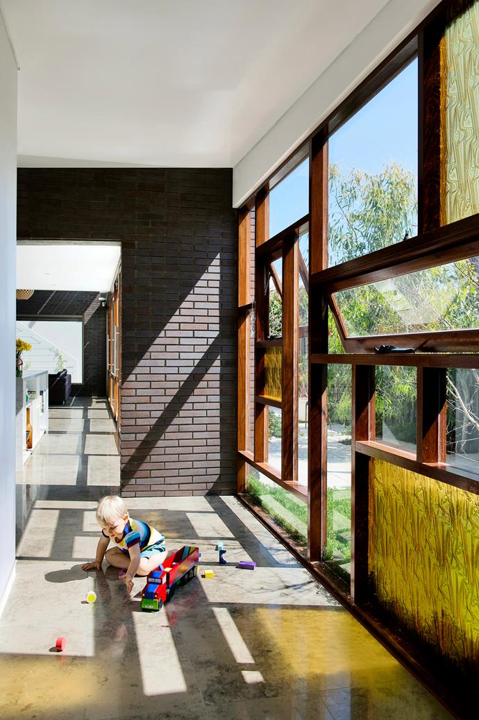 "Henry has plenty of play space in the sunny vestibule area, the transition point between the old and new sections of the home.   Bowral Blue slimline **glazed bricks** from [Austral Bricks](http://australbricks.com.au/|target=""_blank""). Amber **glass panels** from [Glass Australia](http://www.glassaustralia.com/