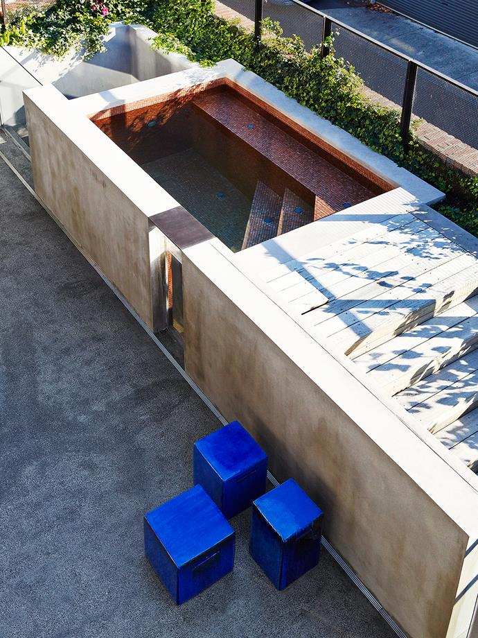 "The view from upstairs over the plunge pool that is finished in bronze mosaic tiles. Also showing are [Gervasoni](http://www.gervasoni1882.it/en|target=""_blank"") InOut stools."