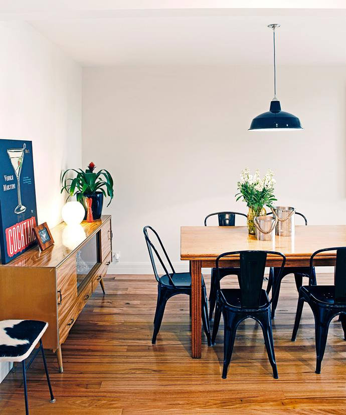 An industrial-style pendant light and vintage poster really liven up this living room. Photo: Julian Kingma / bauersyndication.com.au