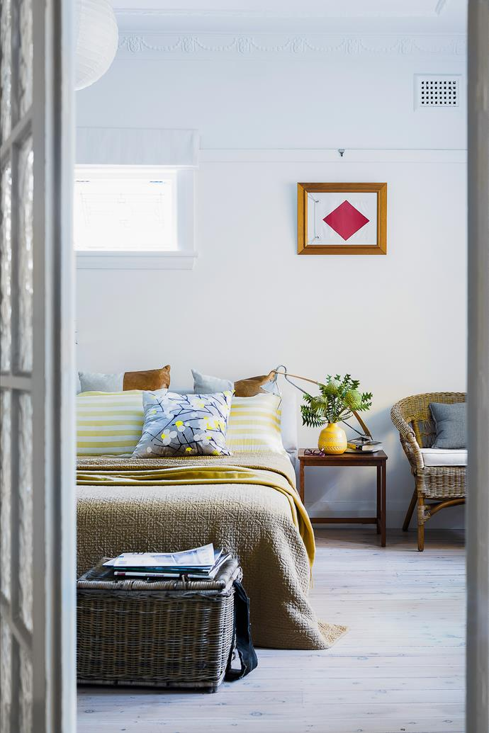"""They may have downsized to a smaller house, but Dianne and David found room for their favourite furniture in the main bedroom, including the bedside table, wicker chair and an inherited basket. The original cypress floor was limewashed. A semaphore flag was framed as an artwork.   **Cushions**, **bedlinen** and **throw**, all from [Busatti](http://busatti.com.au/