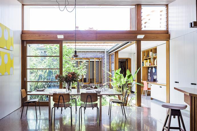 """""""The wide panels of glass and the floating roof are the main reasons the open-plan area feels so light,"""" says owner David. He and Dianne have owned the pendant light and dining table for 20-odd years.   Vintage dining **chairs** from [Vampt Vintage Design](http://vamptvintagedesign.com/