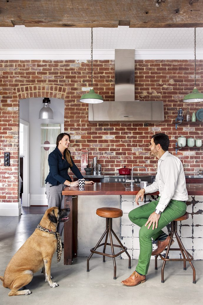 "Carla, Ben and Yoko the mastiff-ridgeback cross in the open-plan kitchen. The recycled bricks ""give the spaces character and age"", says Carla. ""We wanted the imperfections in them to remain."" The rangehood, sink and benchtops came from a commercial kitchen; the green pendant lights were picked up at a New York flea market.   Vintage **stools** from [Mulbury](http://www.mulbury.com.au/
