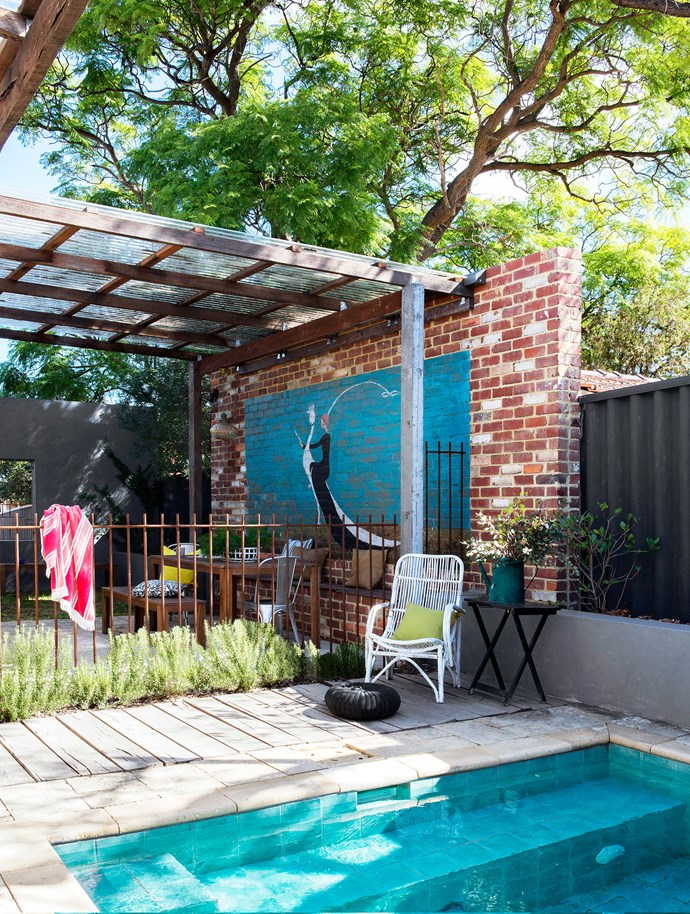 The pool fence, made by Ben from steel-reinforcing bars, is designed to rust and add character to the outdoor courtyard. The wicker chair was rescued from the roadside and refreshed with white paint. The reclaimed limestone pavers are easy to maintain and develop a beautiful patina over time.