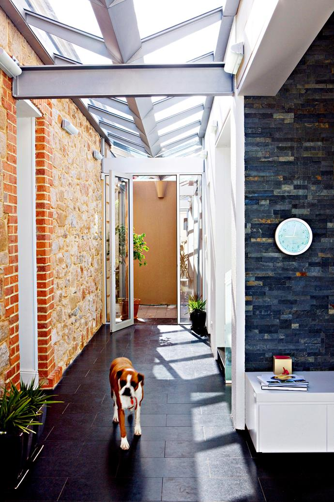 """In this Adelaide home designed by heritage architect Bruce Harry, the hallway links the original 1890s sandstone building with the home's extension, which is finished with a bookleaf slate veneer. A custom-made inverted skylight spans the hall, welcoming light in. The floor is a honed granite in charcoal black from [Hall Granite](http://www.hallgranite.com.au/