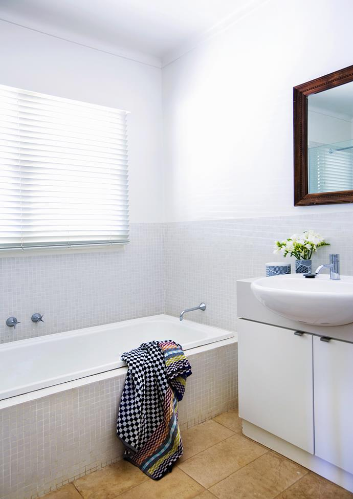 The bathroom with its luxurious tub is a favourite escape for the family of six. Space-saving ideas were implemented when renovating the compact room, including installing a semi-recessed basin and wall-mounted tapware.