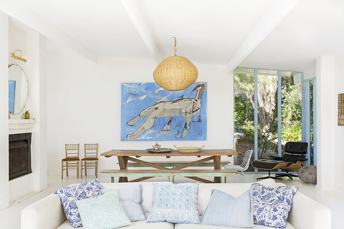 """A palette of soft blues, white and timber creates a relaxed beachy vibe in the open-plan living area. The artwork is an interpretation of the Barrenjoey Headland by [George Raftopoulos](http://www.georgeraftopoulos.com/ target=""""_blank"""")."""