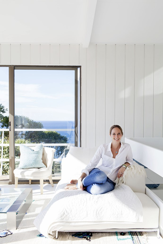"""Heidi sits in her favourite spot of the beach house – the light and airy top """"tower"""" storey, which comprises the master bedroom, study, and a living space the family call the """"cocktail area""""."""