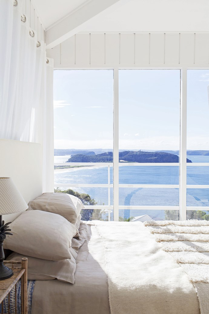 The master bedroom on the top level of the tower has stunning views of Barrenjoey Headland. The decor is kept simple with a white colour palette and textured blankets.