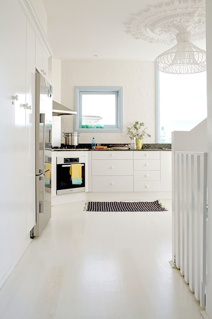 """The kitchen was pink when the Correas bought the house, so for a quick update they painted the doors and floorboards. The pompom mat is from [Paddo To Palmy](http://paddotopalmy.com.au/ target=""""_blank"""")."""