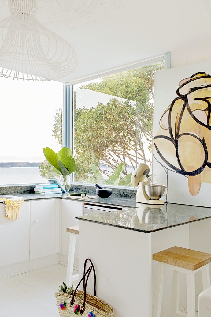 """Simple white kitchen cabinetry allows the amazing view over Palm Beach and Pittwater to take centre stage. The striking artwork is by [Henry Curchod](http://www.henrycurchod.com/ target=""""_blank"""")."""